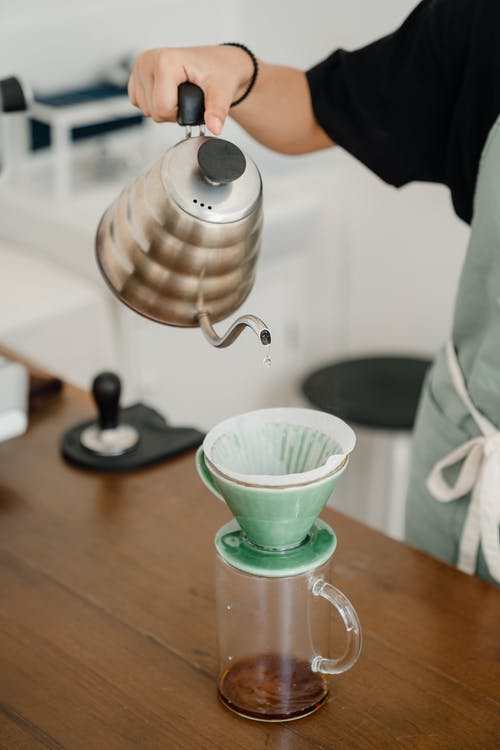 Crop barista brewing coffee with pourover filter