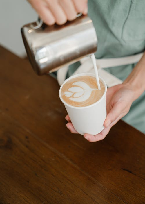Crop barista pouring steamed milk into cup with coffee