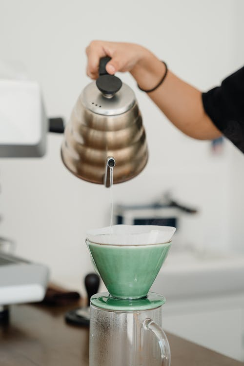 Crop barista pouring water into pourover