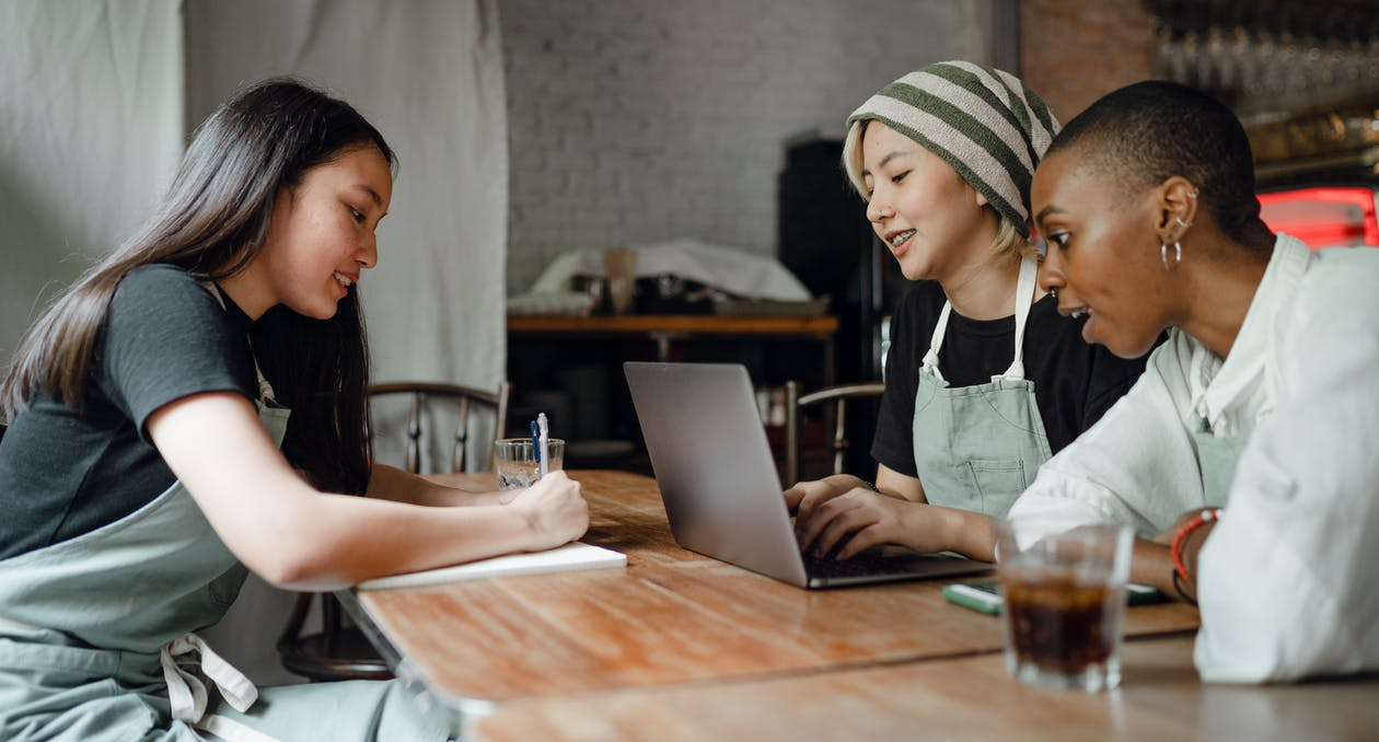 Positive smiling multiethnic female coworkers wearing casual clothes and aprons sitting at wooden table with modern laptop and taking notes while working on project together in creative workplace