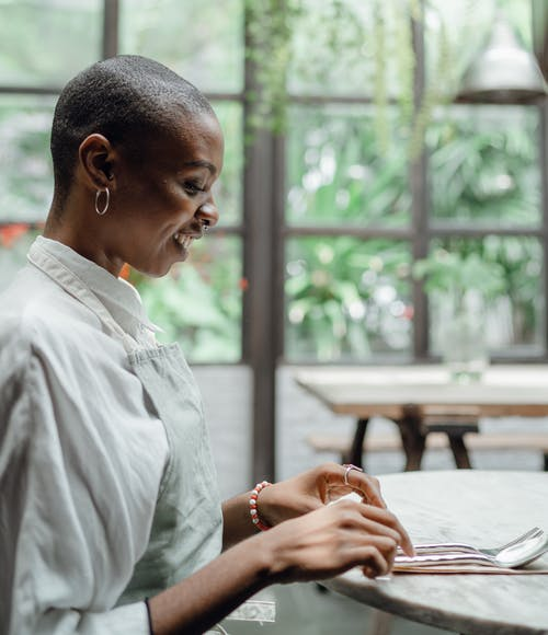 Cheerful black woman sitting at table in restaurant