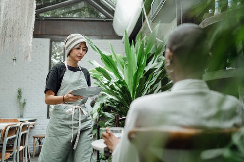Positive young ethnic waitress in hat and apron carrying plate with meal and serving female guest while working in creative restaurant full of lush green plants
