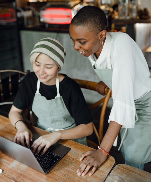 Cheerful waitresses typing on laptop in cafe