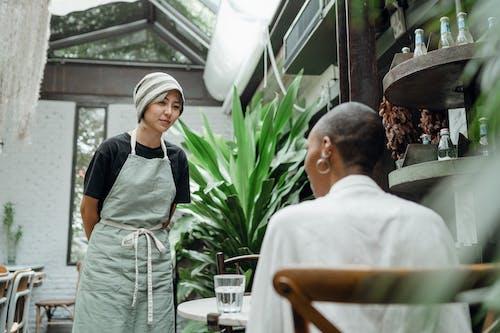 Positive waitress taking order from customer