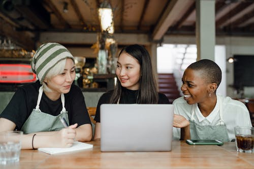 Smiling positive multiracial coworkers wearing aprons browsing modern netbook and having conversation while sitting at wooden table in cozy cafe
