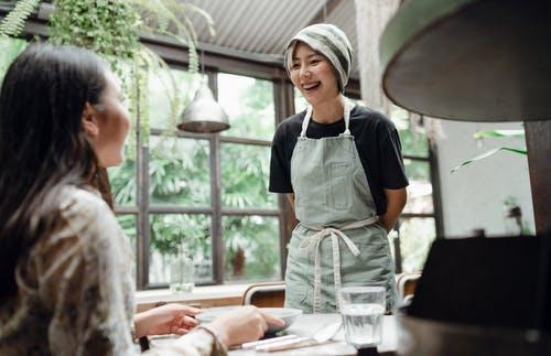 Cheerful waitress serving dish to customer in cafe