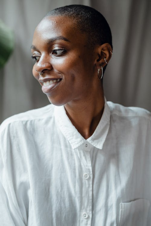 Cheerful black woman in white blouse looking away