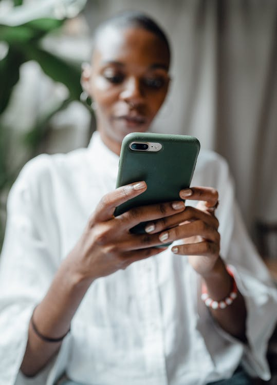 Black woman messaging on modern cellphone