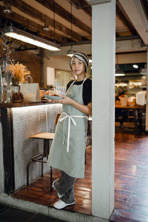 Positive young Asian waitress in apron and hat with plate leaning on beam and looking at camera before serving food in cozy modern restaurant