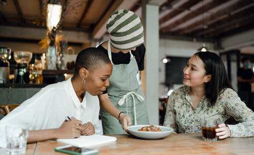 Cheerful women tasting new menu food in cafe