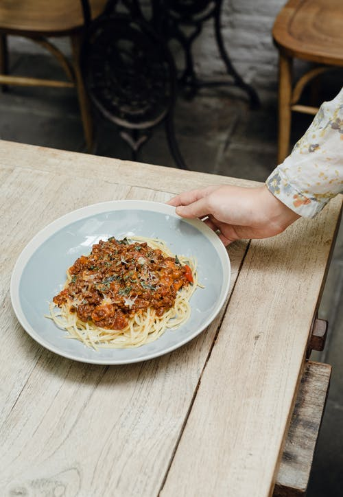 From above crop anonymous female serving delicious Italian spaghetti bolognese on wooden shabby table in cafe