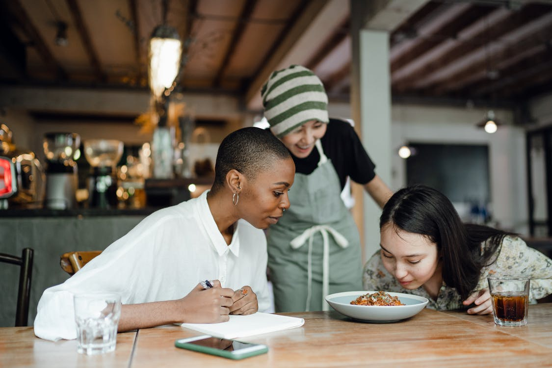 Cheerful coworkers tasting and smelling food in restaurant