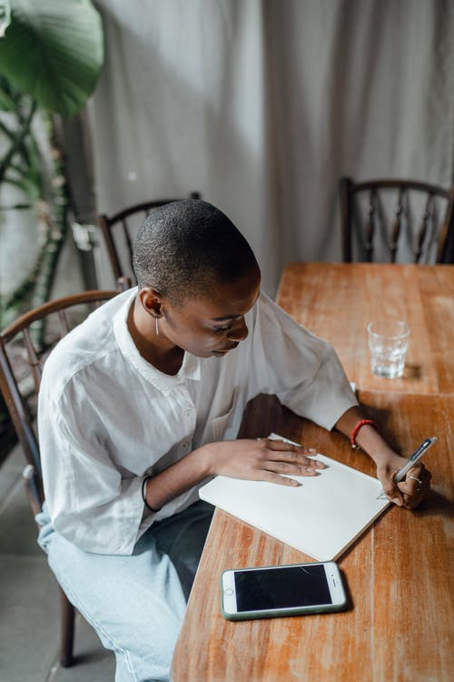 From above of black left handed female in casual wear taking notes in notepad while sitting at shabby table with smartphone against gray curtains