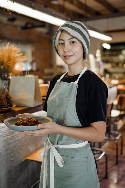 Positive waitress carrying plate with delicious food