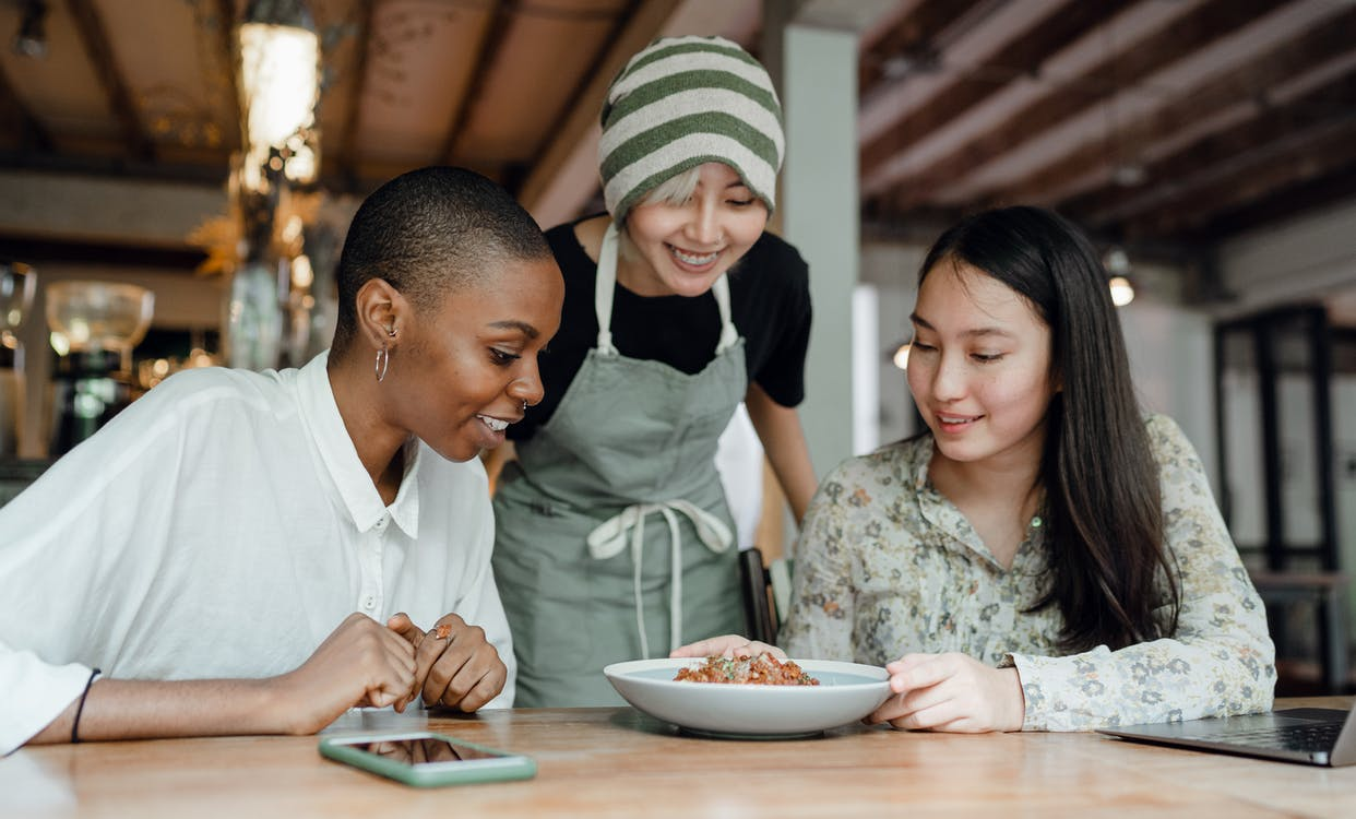 Happy friends tasting food in cafeteria