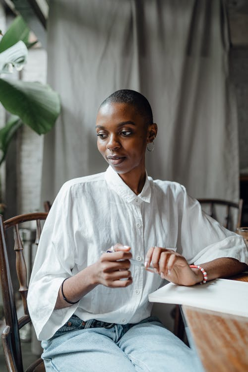 Pensive young bald African American female in white shirt relaxing in cafe on sunny day