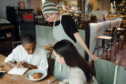 Positive young Asian waitress in apron and hat serving delicious pasta for interested diverse female customers in cozy cafe