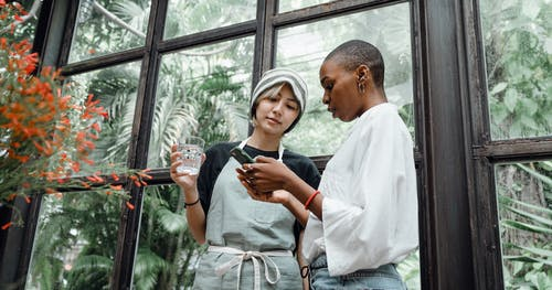 Focused young diverse female colleagues browsing smartphone and talking to each other