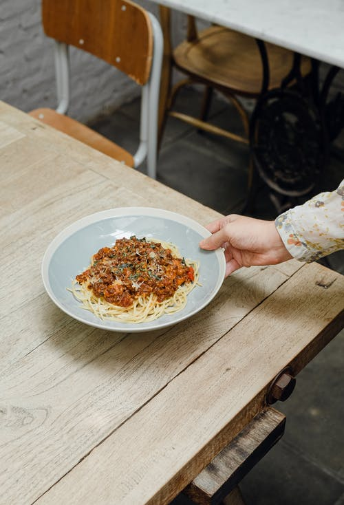 Crop woman putting plate of spaghetti bolognese on table