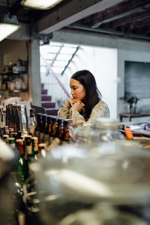 Side view of thoughtful young Asian lady with long dark hair sitting at counter in bar with laptop leaning on chin