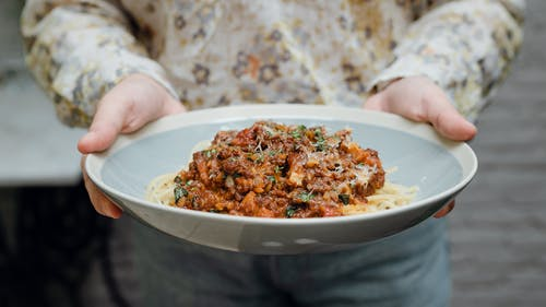 Crop young lady holding plate of pasta bolognese