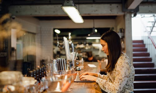 Focused young Asian woman working on laptop in pub