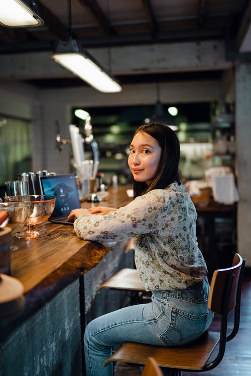 Cheerful young ethnic woman typing on netbook during work in bar