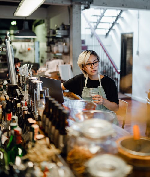Focused young ethnic female bartender drinking water at counter in pub