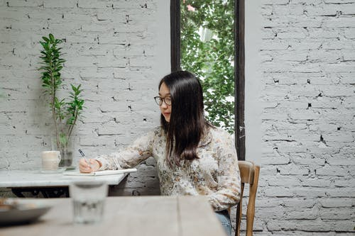 Young Asian woman writing in notebook sitting against white brick wall in modern cafe