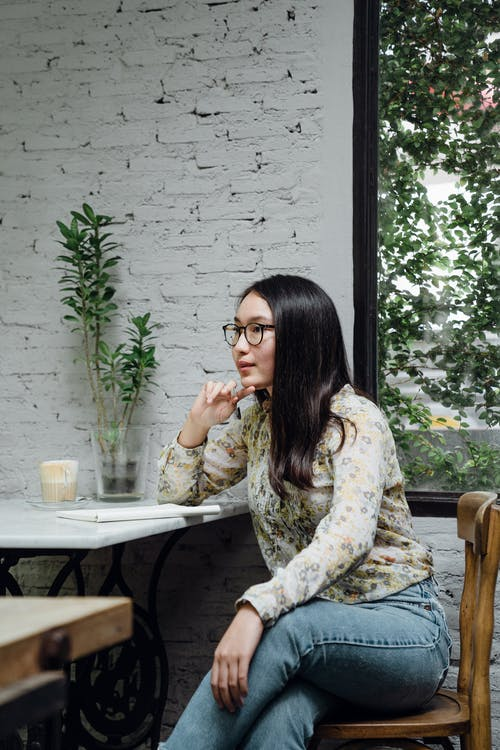 Focused young ethnic female entrepreneur in casual clothes and eyeglasses thinking about business ideas while working remotely in cozy cafe
