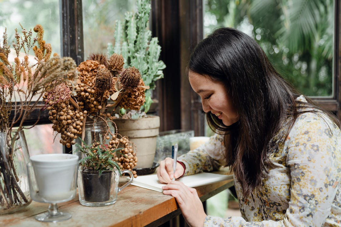 Happy young ethnic woman writing article in cozy workplace