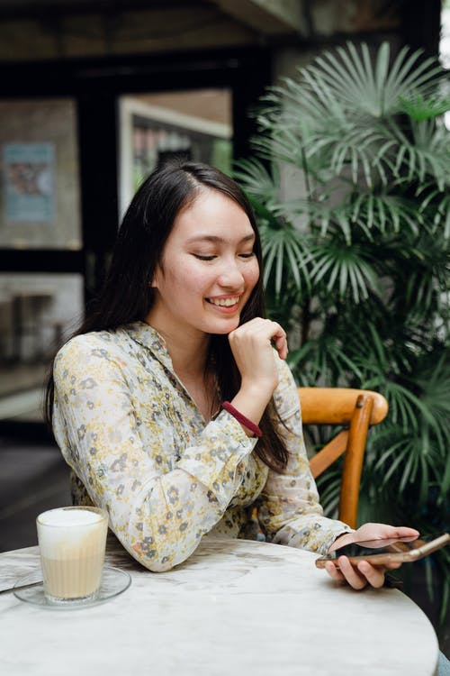 Cheerful young Asian woman calling on smartphone sitting in outdoor cafe