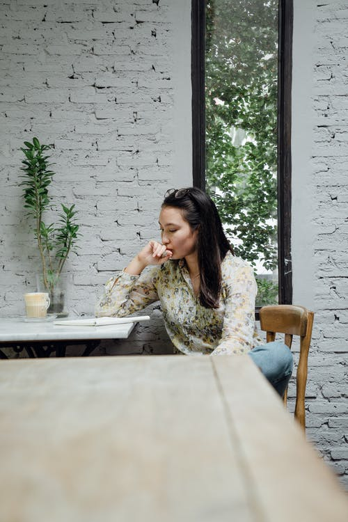 Focused young Asian woman thinking about project in cafeteria