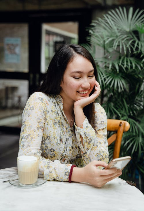 Smiling young Asian woman sitting in cafe with chin on hand and using smartphone