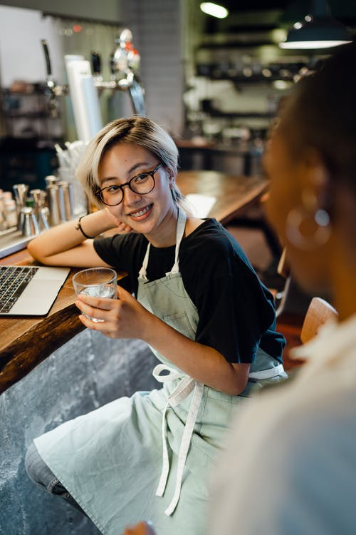 Smiling young ethnic woman drinking water and talking to colleague at bar counter
