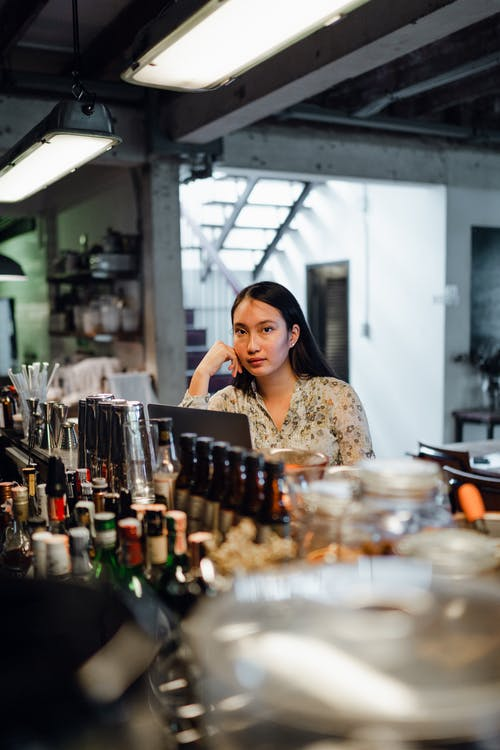 Concentrated young ethnic woman using netbook sitting at bar counter