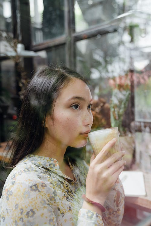 Pensive woman sipping hot latte behind window