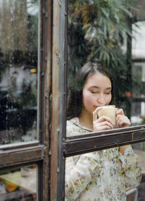 Dreamy woman enjoying hot aromatic latte