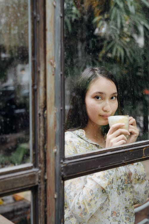Dreamy woman with cup of latte