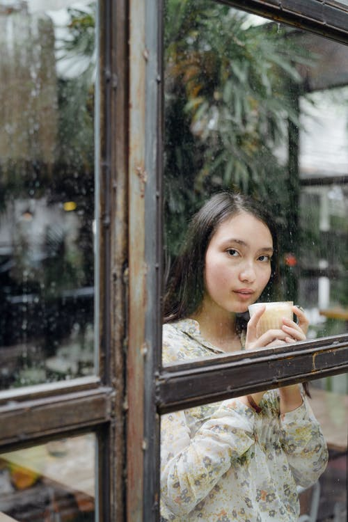 Pensive woman with glass of coffee standing behind big window