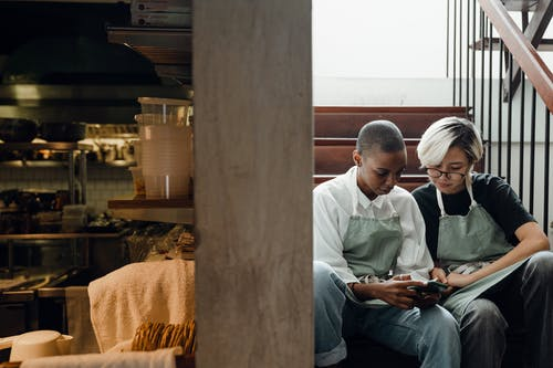 Focused young multiracial waitresses resting with smartphone during break