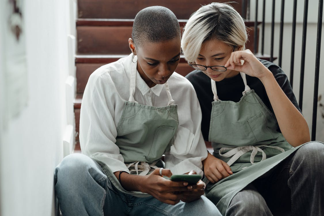 Concentrated young diverse girlfriends watching video on smartphone