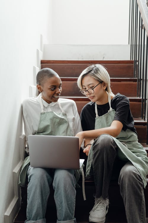 Young smiling diverse female friends in aprons sitting on stairs and working on project using laptop