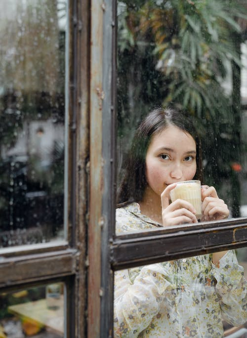 Pensive young ethnic woman drinking latte in cafe against window