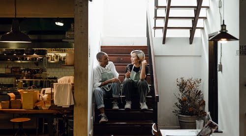 Full length of cheerful young multiracial waitresses in aprons talking to each other while resting on staircase near restaurant kitchen during break
