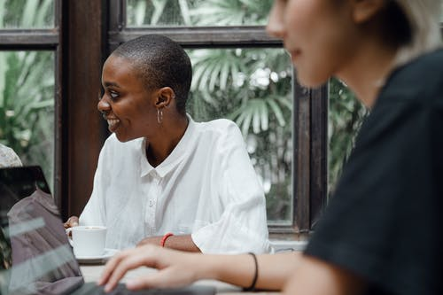 Optimistic young diverse female colleagues working on laptop and drinking coffee