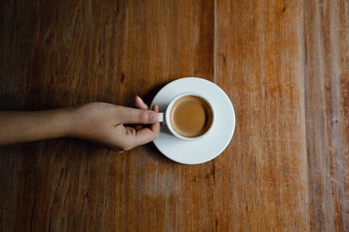 Crop person with cup of coffee at wooden table