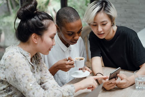 Diverse female friends checking social media on mobile in cafe