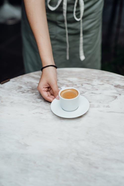 Crop barista serving cup of coffee