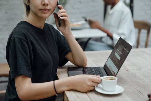 Crop Asian lady in black tee making phone call while sitting at table with coffee and laptop in cafe